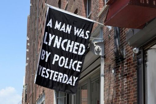 """Dread Scott's """"A Man Was Lynched by Police Yesterday"""" Flag Should Fly outside MoMA"""