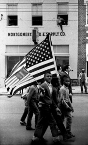 Young boys marching with American Flags past Montgomery Feed & Supply Co., with man perched on upper floor window sill, March 25, 1965