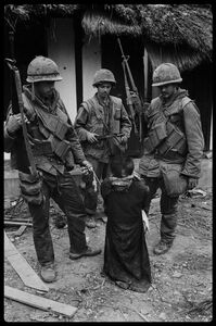 US Soldiers tormenting a civilian in the old city of Hue during the offensive, Tet, Hue