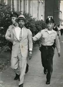 Two Police Officers, Unaware Of Their Prisoner's Identity, Hustle Dr. Martin Luther King Away From The Montgomery Courthouse Where He Had Been Arrested For Loitering