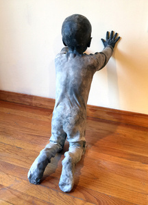 Figure of a child kneeling and leaning on the wall