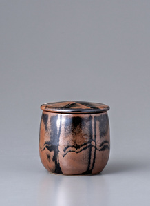 Lidded container, kaki and black glazes with wax resist decoration