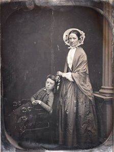 A Woman in Bonnet & Shawl, with Her Seated Son