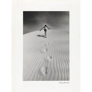 Femme nue gravissant une dune