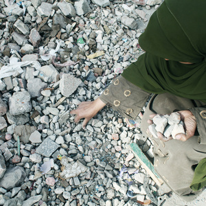 Egypt's Revolution, A woman collects rocks and keep on repeating she will not go until Moubarak goes. Cairo, Egypt