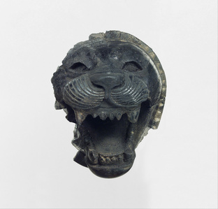 Furniture element carved in the round with the head of a roaring lion