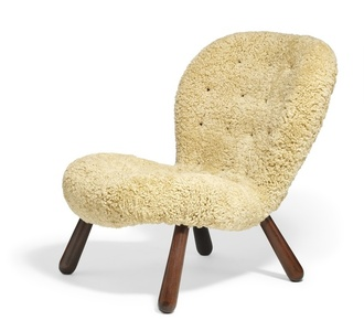 """Clam"". Easy chair with stained oak legs. Seat and back upholstered with light brown sheepskin, fitted with buttons."