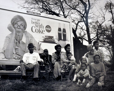 Coca Cola lady looking over black multi-generational family seated on hillside under sign, watching 1965 Selma to Montgomery civil march pass by, March 25, 1965