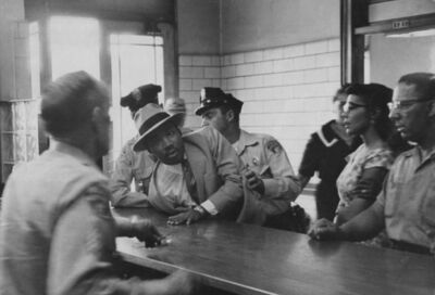Charles Moore, 'Martin Luther King Jr.is Arrested for Loitering Outside a Courtroom Where his Friend Ralph Albernathy is Appearing for a Trial. As His Wife Looks on, King is Sprawled Across the Police Desk', 1958