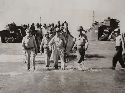 Gen. Douglas MacArthur with Gen. Richard Sutherland and Col. Lloyd Lehrbas walks through the surf to the beach at Lingayen, Luzon, the Philippines