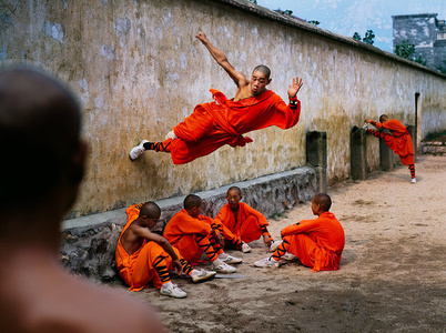 A young monk runs along the wall over his peers at the Shaolin Monastery in Henan Province, China