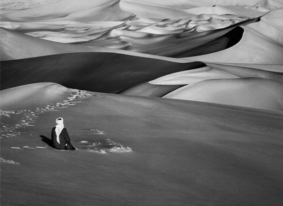 Man praying in the sand dunes in Maor, Tadrart, South of Djanet, Algeria