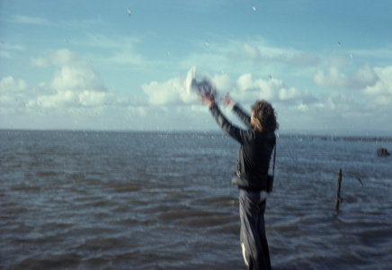 Releasing a seagull, Morecambe Bay, Lancashire, November 1976