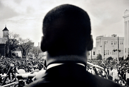 Dr. Martin Luther King, Jr., seen from his back, speaking before 25,000 civil rights marchers, in front of the Alabama state house - 1965 Selma to Montgomery, Alabama Civil Rights March - March 25, 1965