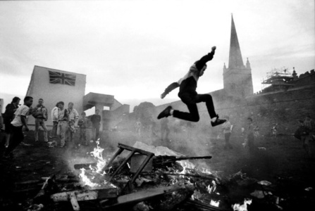 Protestant youth play around a bonfire in a working class housing estate in Derry, Northern Ireland