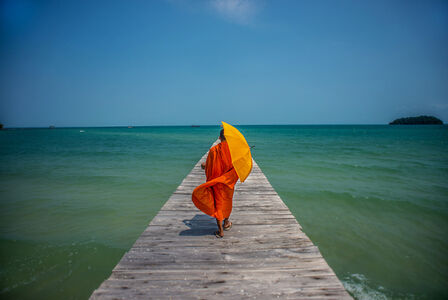 A novice monk waits for a local boat ride to the mainland from Koh Rong, Island in Cambodia