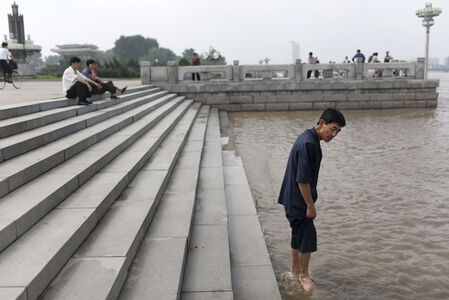 A man wades into the Tae Dong river where banks are flooded high above the normal water level in Pyongyang, North Korea