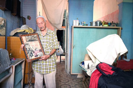 A member of the Sefarati Synagogue shows a photograph of his parents
