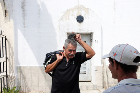 A member of the Jewish community puts on his Kipa before entering the Sefarati Jewish cemetery outside of Havana