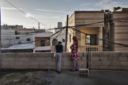 Mohammed, 20, and his sister Mirna, 26, watch a gun fight next to their home. They live in the Rashidiyeh camp for Palestinian refugees