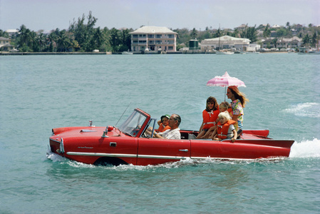 "Sea Drive, 1967: Film producer Kevin McClory takes his wife Bobo Segrist and their family for a drive in an ""Amphicar"" across the harbour at Nassau, Bahamas"
