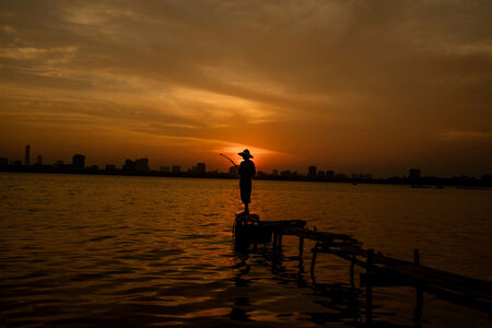 An urban fisherman takes in the last hours of daylight overlooking West Lake in Hanoi, Vietnam.
