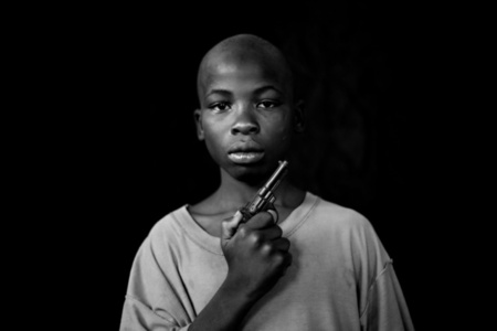 A Boy with his toy pistol, Growing in Darkness Series