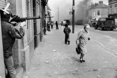 Catholic West Belfast Ð Falls Road Ð Hijacked vehicle burns tin the background marking the anniversary of the British Policy of internment without trial. Northern Island, Great Britain