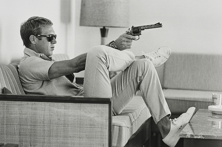 Steve McQueen aims a pistol in his living room, California