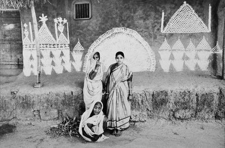 Three Oriya women in front of their house with a wall painted by them using rice flour