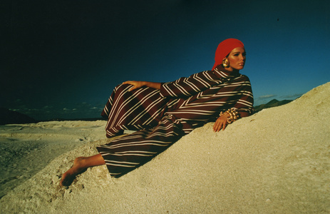Ann Turkel reclining on sand dune in brown-striped caftan & red scarf