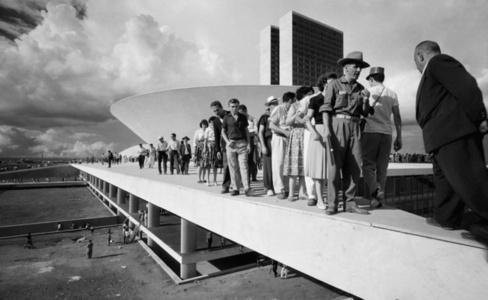 Populares sobre cobertura do palácio do Congresso Nacional no dia da inauguração de Brasília