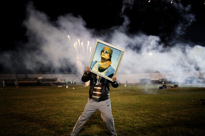 Moises Saman, 'A Qaddafi supporter holds a portrait of the Libyan leader as fireworks go up in the background on a soccer field in a suburb of Zawiyah where government minders took a group of foreign journalists to attend a staged celebration.', 2011