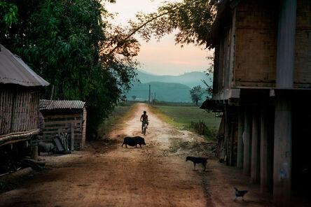 Steve McCurry, 'Boy Rides Bike Down Dirt Road'