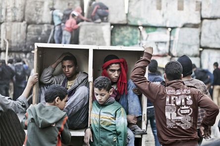 Moises Saman, 'Young protestors take shelter behind a barricade during clashes with Egyptian police on the second anniversary of the Revolution. Cairo, Egypt. ', 2013