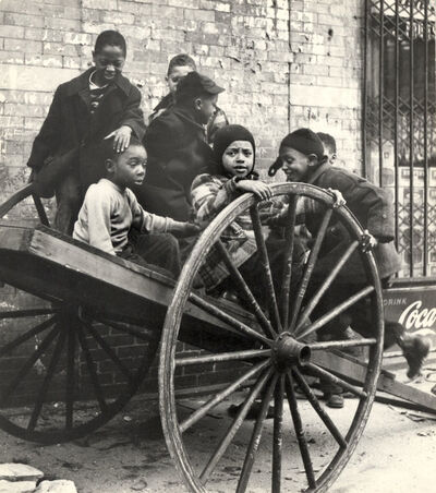 Leo Goldstein, 'Group of Children Playing on Wooden Cart with Huge Wheels, New York City', ca. 1950