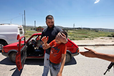 Moti Milrod, 'A Palestinian man holds a boy's head after Jewish settlers threw stones at their car, south of Nablus in the West Bank. The settlers threw stones at Palestinians during the funeral procession of Ben Yosef Livnat, a 25 year old shot to death by Palestinian policemen at Joseph's Tomb holy site in Nablus', 2011