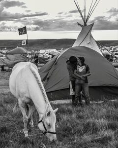 Ryan Vizzions, ' Hiding from view of nearby families, a young couple sneaks in a quick kiss while allowing a horse to graze on Oceti Sakowin grass, September 8, 2016'