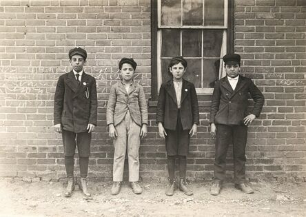 Lewis Wickes Hine, 'Sweepers and mule-room boys in Royal Mill, River Point, R.I. Boy left hand end, Manuel Mites has been in mill 2 years. Clinton Silvey and Louis Perry (centre boys) have been in mill one year and said they are now 12 years old. Boy on right hand Manuel Silvey been in mill 1 year. (They could not speak English.) Location: River Point, Rhode Island.', 1909