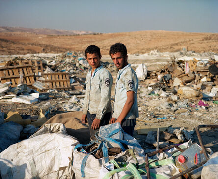 Nir Kafri, 'Brothers Ahmed and Mahmoud of Yatta village, near Hebron, collect metal scraps at the nearby landfill in hopes to sell it for a small profit. They are wearing Israeli police shirts found in the trash. November, 2012 ', 2012