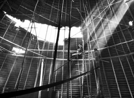 """Sebastião Salgado, 'Kwakway works to finish the straw roof of his oca. The house's structural columns, made of large tree trunks, are installed by a group of men working together. Then the straw roof will be installed entirely by the """"owner"""" of the house, whose name the house will bear. [...] Suruwahá Indigenous Territory, state of Amazonas', 2017 [printed on request]"""