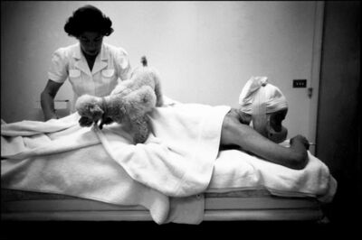 Eve Arnold, 'Actress Joan Crawford, during a massage session, with her poodle walking over her back, at home in Hollywood. Hollywood, California. USA.', 1959