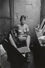 Stripper with bare breasts sitting in her dressing room, Atlantic City