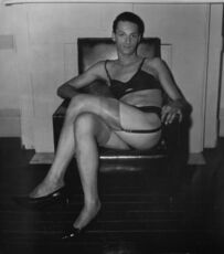 Seated man in a bra and stockings, N.Y.C.