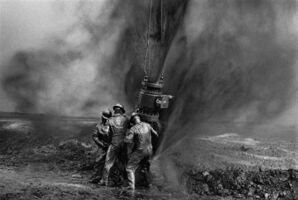Sebastião Salgado, 'Workers struggle to remove bolts from the remains of an old wellhead. Working with metal tools can produce sparks, threatening to consume everything in flames, Oil Wells, Greater Burhan, Kuwait', 1991