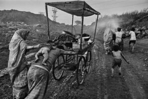 Sebastião Salgado, 'A family leaves an open-cut coal mine with a cart used to bring food to workers. Dhanbad, Bihar State, India.', 1989