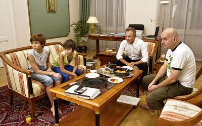 """G.R.A.M., '""""Barak Obama mit seiner Frau Michelle und seinen beiden Töchtern Sasha (13, links) und Malia (10). Ein großer linker Zeh unter dem Tisch verrät, dass es sich auch der US-Präsident barfuß bequem gemacht hat.""""', 2011"""
