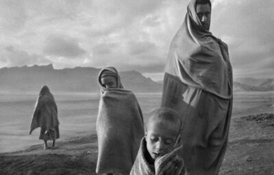Sebastião Salgado, 'Draped in blankets to keep out the cold morning wind, refugees wait outside Korem camp, Ethiopia', 1984