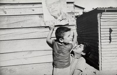 Paola Agosti, 'Santiago del Cile due bambini in un quartiere di periferia giocano con un manifesto di Salvador Allende', 1970