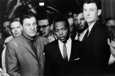 """Charles Moore, 'Sept. 30, 1962 — Chief U.S. Marshal James McShane and Assistant Attorney General for Civil Rights John Doar guard James Meridith from harm, as Federal marshals under direction of President John F. Kennedy, arrive at the University of Mississippi (""""Ole Miss"""") to allow Meredith admission, against actions by the University and governor, and with much student protest.', 1962"""